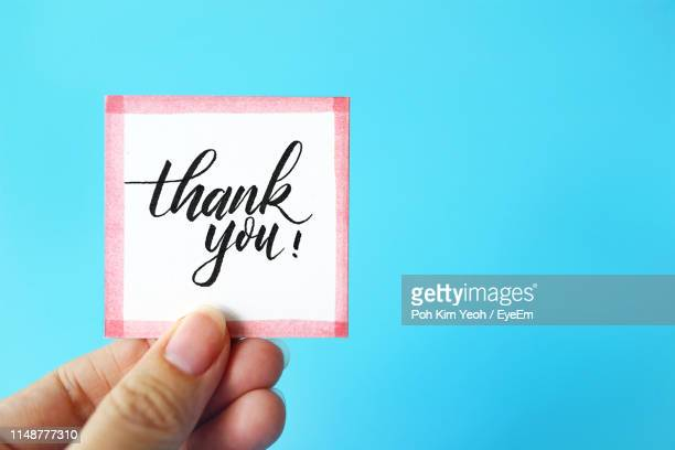 cropped hand holding thank you text against blue background - thank you stock pictures, royalty-free photos & images