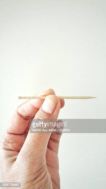 Cropped Hand Holding Toothpick Against White Background
