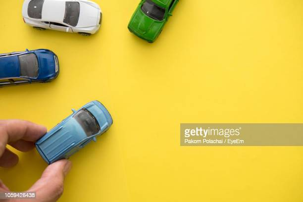 cropped hand holding toy car against yellow background - toy car stock pictures, royalty-free photos & images