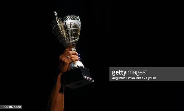 cropped hand holding trophy against black background - trophy stock pictures, royalty-free photos & images
