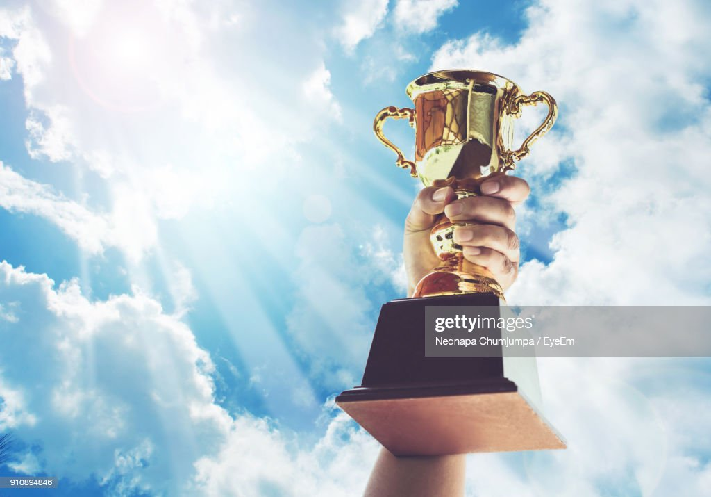 Cropped Hand Holding Trophy Against Cloudy Sky : Stock Photo