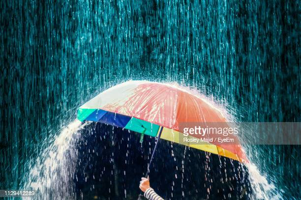 cropped hand holding umbrella during rainfall - torrential rain stock pictures, royalty-free photos & images