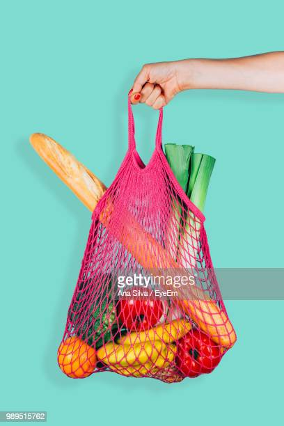 cropped hand holding vegetables in bag - バッグ ストックフォトと画像