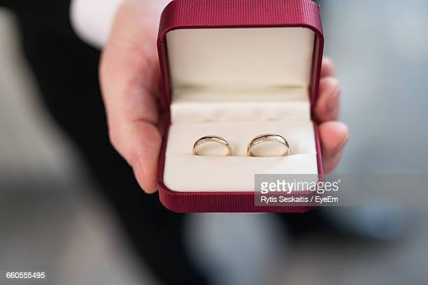 cropped hand holding wedding rings in box - wedding ring stock pictures, royalty-free photos & images