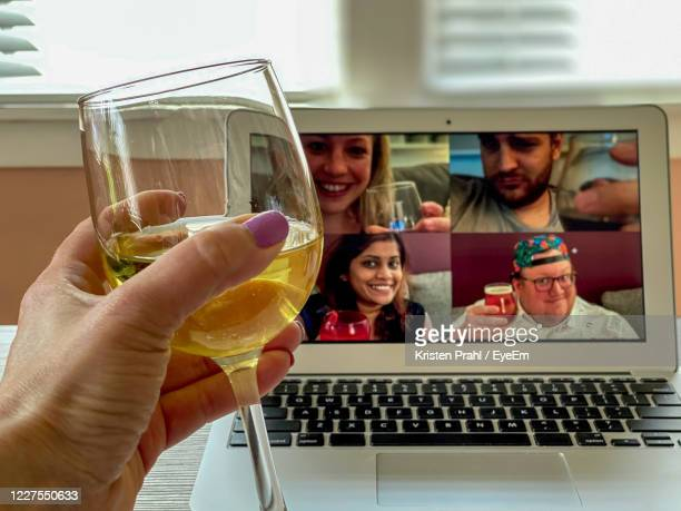 cropped hand holding wineglass against laptop - happy hour stock pictures, royalty-free photos & images