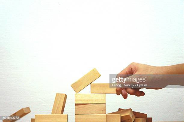 Cropped Hand Holding Wooden Block While Playing Game Against White Background