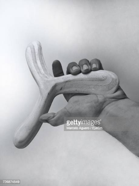 Cropped Hand Holding Wooden Boomerang By Wall