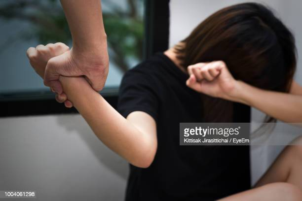 cropped hand holding wrist of woman at home - domestic violence stock pictures, royalty-free photos & images