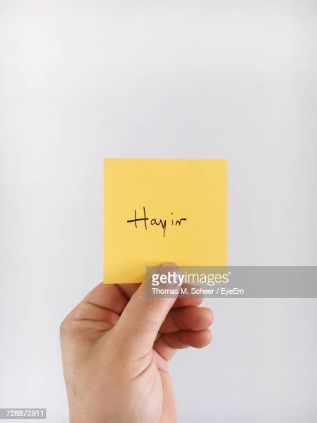 Cropped Hand Holding Yellow Sticky Note With Text Against White Background