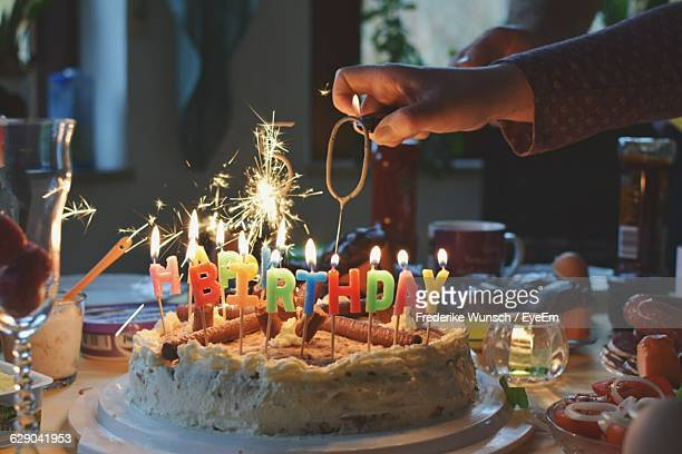 Cropped Hand Igniting Candle On Birthday Cake At Home
