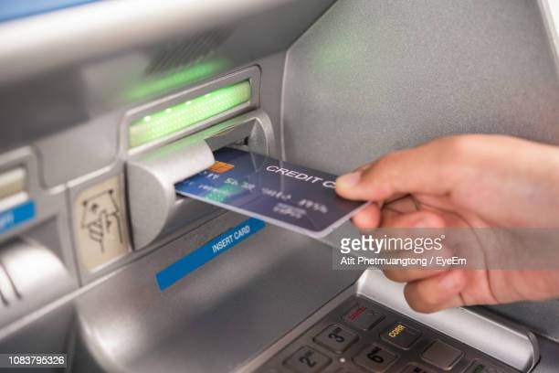 cropped hand inserting credit card in atm machine - atm stock pictures, royalty-free photos & images