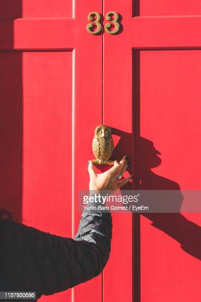 cropped hand knocking door - knocking on door stock photos and pictures