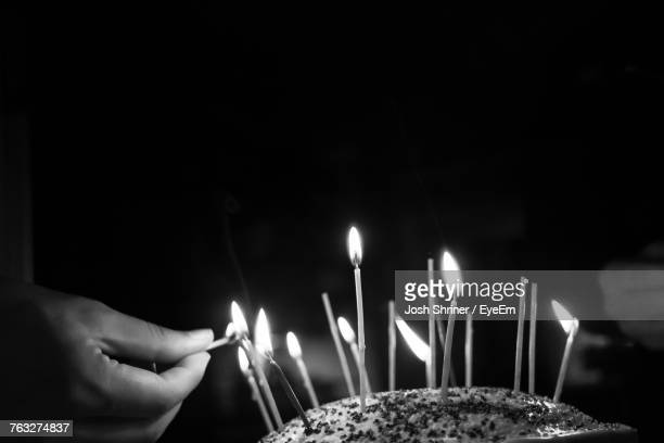 Cropped Hand Lighting Candles On Cake