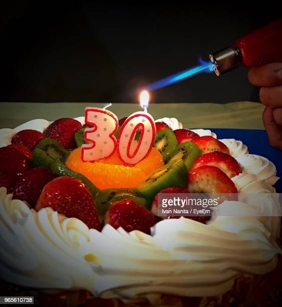 Cropped Hand Lighting Number 30 Candle On Birthday Cake