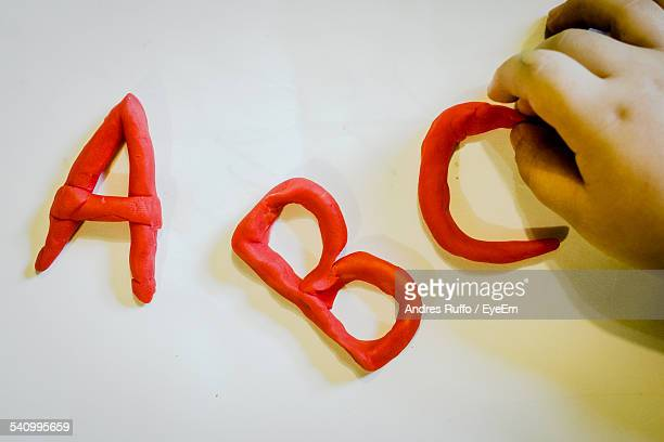 Cropped Hand Making Alphabets With Modelling Clay On White Table