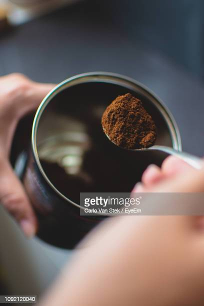 cropped hand making coffee at table - ground coffee - fotografias e filmes do acervo