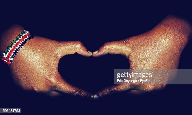 Cropped Hand Making Heart Shape In Black Background