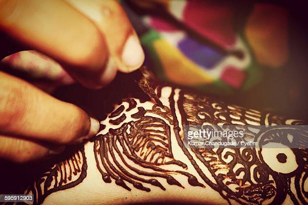 Cropped Hand Making Henna Tattoo On Woman Hand