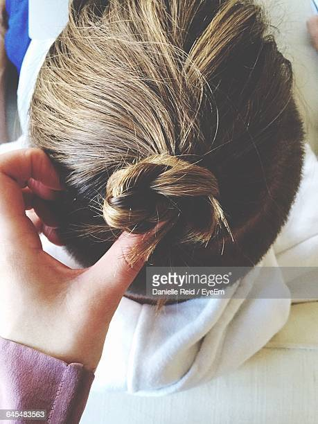 cropped hand making man hair bun - danielle reid stock pictures, royalty-free photos & images