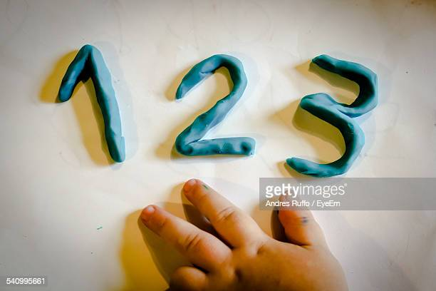 Cropped Hand Making Numbers With Modelling Clay On White Table