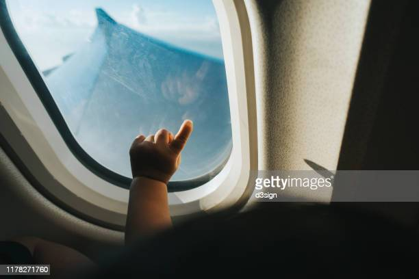 cropped hand of a toddler pointing airplane window against blue sky while travelling - man made stock pictures, royalty-free photos & images