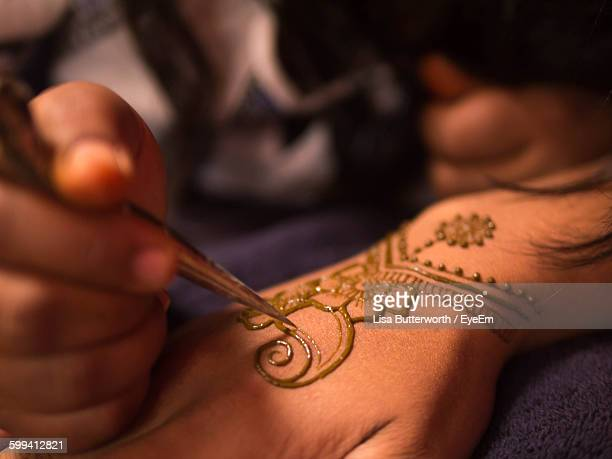 Cropped Hand Of Artist Drawing Henna Tattoo