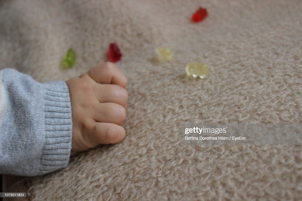 Cropped Hand Of Baby On Carpet : Stock-Foto