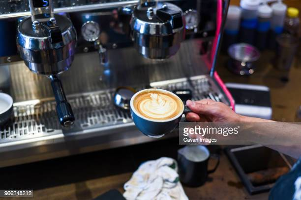 cropped hand of barista holding frothy drink by coffee maker at cafe - coffee drink stock pictures, royalty-free photos & images