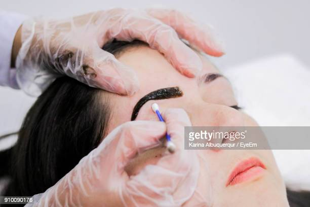 cropped hand of beautician using cotton swab on female customer - eyebrow stock pictures, royalty-free photos & images