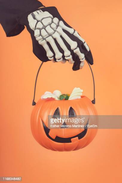 cropped hand of boy with skeleton glove holding jack o lantern basket against orange background - basket stock pictures, royalty-free photos & images
