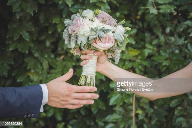 cropped hand of bride giving bouquet to groom - 結婚式 ストックフォトと画像