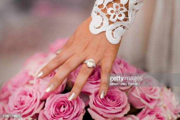 cropped hand of bride touching bouquet in wedding ceremony - diamond ring stock pictures, royalty-free photos & images