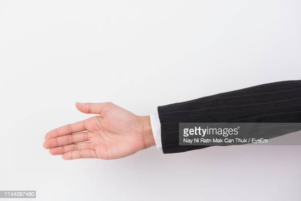 cropped hand of business person over white background - 袖 ストックフォトと画像