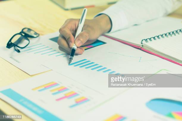 cropped hand of businessman analyzing graphs on desk - publication stock pictures, royalty-free photos & images