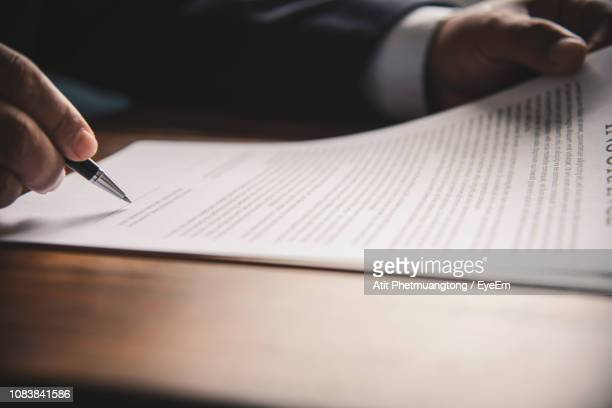 cropped hand of businessman signing on document - signing stock pictures, royalty-free photos & images