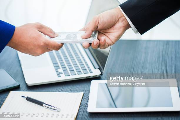 Cropped Hand Of Businessmen Giving Paper Currency To Coworker In Office
