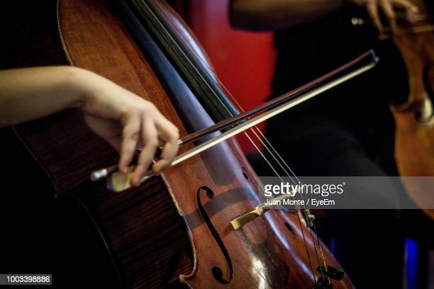 cropped hand of cellist playing cello on stage - cellist stock pictures, royalty-free photos & images