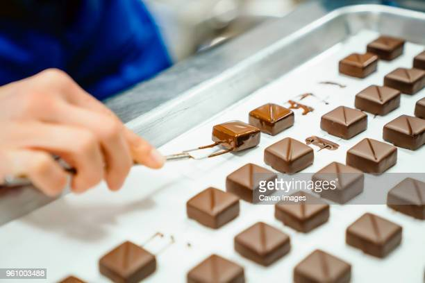 Cropped hand of chef arranging chocolates pieces with dipping fork in tray