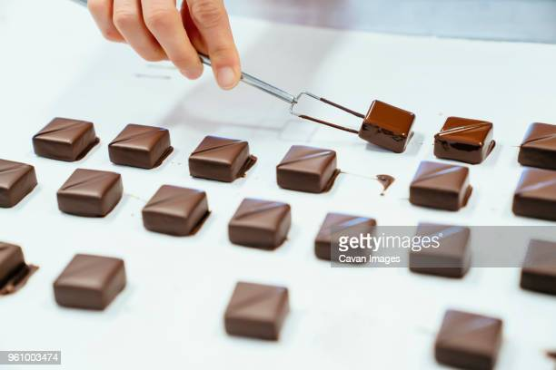 cropped hand of chef holding chocolates with dipping fork in tray - chocolate factory stock photos and pictures