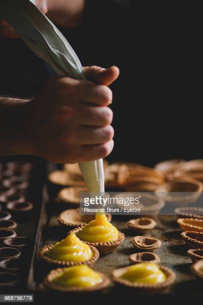 Cropped Hand Of Chef Making Pastries With Piping Bag In Bakery