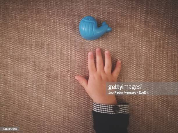 Cropped Hand Of Child By Blue Plastic Toy On Table