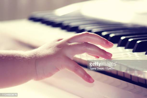 cropped hand of child playing piano - keyboard instrument stock photos and pictures
