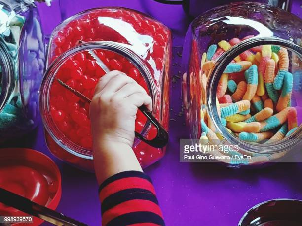 Cropped Hand Of Child Taking Candies From Jar On Table