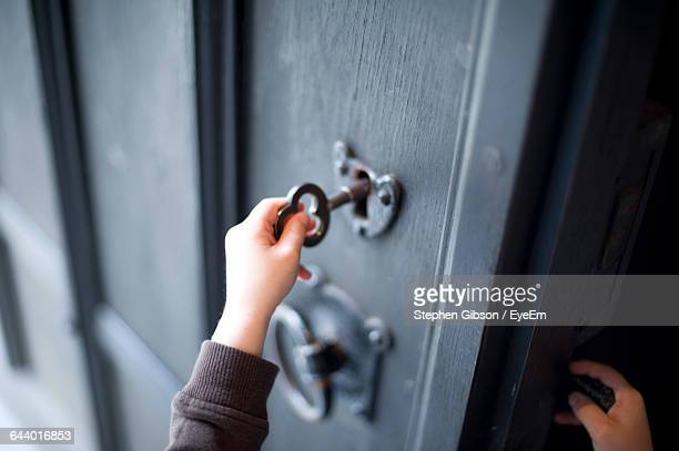 Cropped Hand Of Child Unlocking Door At Home
