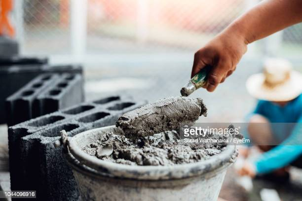 cropped hand of construction worker taking cement from container - cement stock pictures, royalty-free photos & images