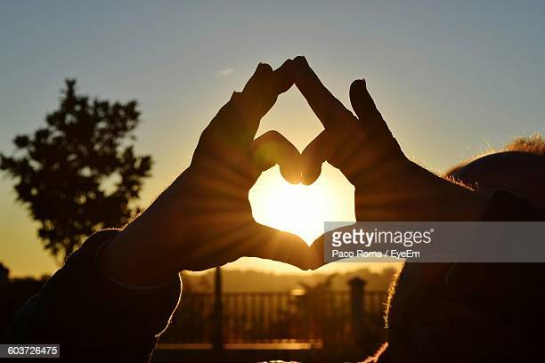Cropped Hand Of Couple Forming Heart Shape Against Sky During Sunset