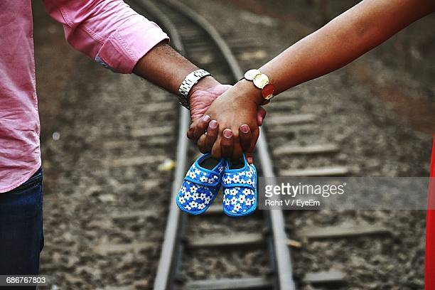 Cropped Hand Of Couple Holding Baby Booties Over Railroad Track