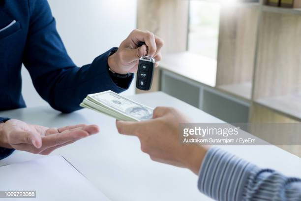 Cropped Hand Of Customer Paying Money To Salesperson Giving Him Car Key