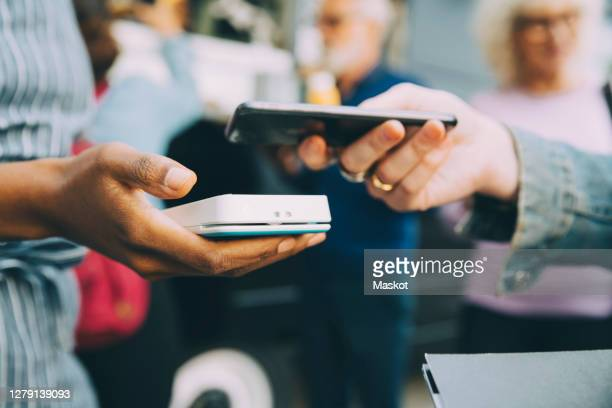 cropped hand of customer paying through smart phone in city - stockholm stock pictures, royalty-free photos & images