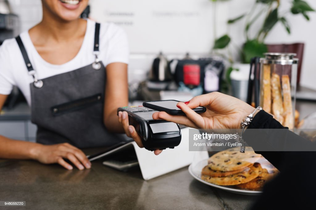 Cropped Hand Of Customer Using Mobile Phone For Contactless Payment To Owner At Cafe : Stock Photo